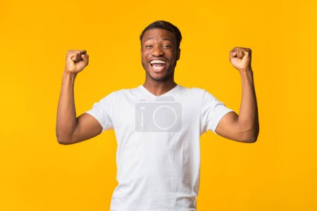Photo for Yes. Joyful Afro Man Shouting And Shaking Fists Celebrating Success Standing Over Yellow Background. Studio Shot - Royalty Free Image