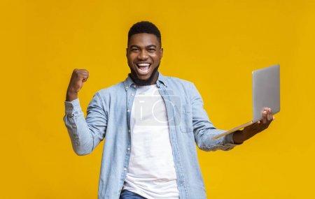 Photo pour Loterie en ligne. Homme africain euphorique tenant un ordinateur portable et se réjouissant du succès, criant et élevant le poing serré sur fond de studio jaune - image libre de droit