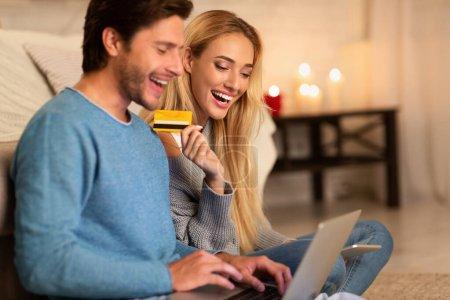 Foto de Pareja alegre que hace la orden en línea usando la computadora portátil y la tarjeta de crédito que se sienta en el piso interior. Enfoque selectivo - Imagen libre de derechos