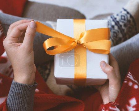 Photo pour Surprise de Noël. Mains féminines ouvrant cadeau de Nouvel An avec ruban jaune, fond flou - image libre de droit