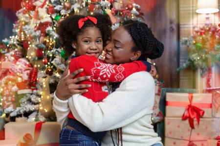 Photo for Cute little afro girl cuddling with her mom near Christmas tree, celebrating winter holidays at home. - Royalty Free Image