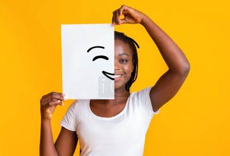 Photo pour Je mets un visage souriant. Fille noire tenant du papier avec le visage souriant imprimé sur, concept de bonheur et de joie - image libre de droit