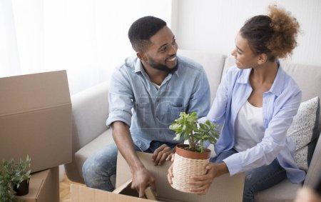 Photo pour Joyeux Afro mari et femme emballant des boîtes de déménagement ensemble assis sur le canapé intérieur. Focus sélectif - image libre de droit