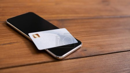 Photo for Online payment. Smartphone with black screen and credit card flat lying on wooden background, closeup - Royalty Free Image