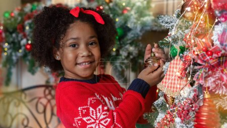 Photo for Cute little black girl playing with bauble on Christmas tree, enjoying winter holidays at home, panorama - Royalty Free Image