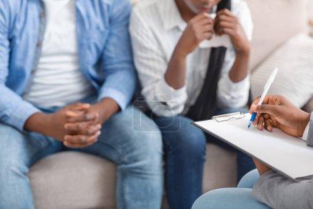 Photo pour Psychologue méconnaissable prenant des notes sur les problèmes des jeunes couples noirs sur la séance de thérapie conjugale au bureau - image libre de droit