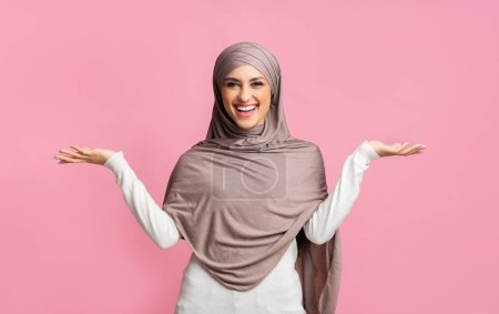 Photo for Cheerful muslim girl in hijab demonstrating something on her empty palms, comparing variants, making scales of her hands over pink background - Royalty Free Image