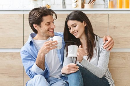 Photo for Morning relax. Cheerful millennial couple with coffee embracing at kitchen - Royalty Free Image