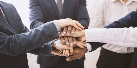 Photo pour Coopération d'entreprise. Empilés mains de l'équipe d'affaires multiethnique, panorama - image libre de droit