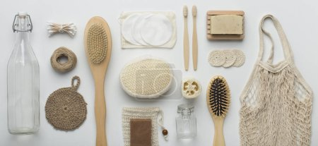 Photo pour Eco friendly. Flat lay of bamboo brushes, eco soap, reusable net bag and glass bottle on white background, panorama - image libre de droit
