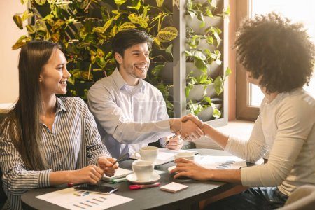 Photo pour Business negotiations. Cheerful partners handshaking in cafe, having agreement, free space - image libre de droit