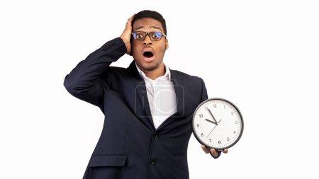 Photo pour Concept de gestion du temps. Homme noir choqué tenant une horloge murale, manque de temps, fond blanc. Panorama - image libre de droit