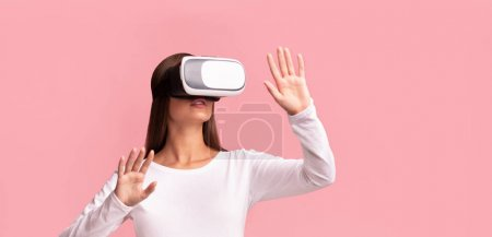 Photo for Virtual Reality. Young Lady In VR Glasses Playing Videogame Standing Over Pink Studio Background. Panorama - Royalty Free Image