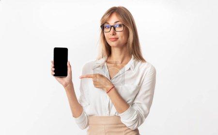 Photo pour Super appli. Femme d'affaires pointant du doigt à l'écran vide de Smartphone recommandant l'application d'affaires debout sur fond blanc de studio. Maquette - image libre de droit