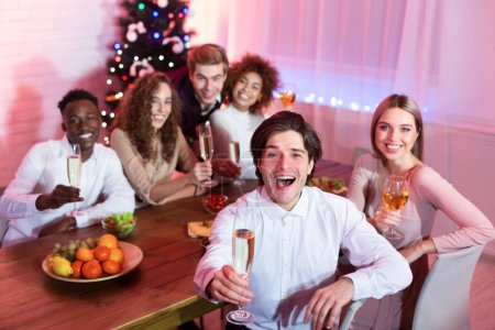 Photo for Cheers. Happy Group Of Millennial Friends Holding Glasses Smiling At Camera Sitting At Table Having Christmas Home Party Indoor - Royalty Free Image