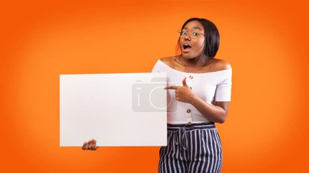 Photo for African American Lady Pointing Finger Holding Blank White Board Posing Over Orange Studio Background. Panorama, Mockup - Royalty Free Image