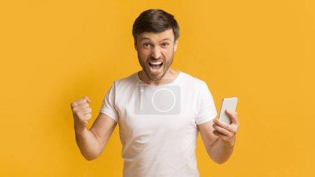 Photo pour Bonne chance. Homme mature émotionnel tenant téléphone portable criant et gesticulant oui debout sur fond de studio jaune. Panorama - image libre de droit