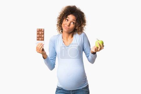 Photo pour Étrangement la femme à la recherche d'un choix entre bonbons et fruits, tenant la pomme et le chocolat, arrière-plan blanc - image libre de droit