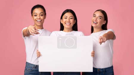 Photo pour Offre pour vous. Three Millennial Girls Holding Blank White Board Advertising Something Standing Over Pink Studio Background. Mockup, Panorama - image libre de droit