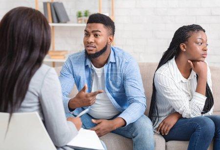 Photo pour Afro-mari Partager les problèmes familiaux assis à côté de sa femme offensée Au bureau des conseillers, orientation sélective - image libre de droit