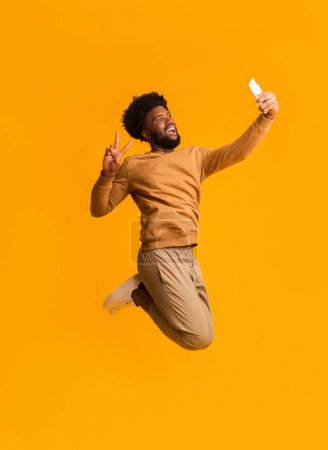 Foto de Amador selecto. Hombre emocional negro que se toma selfie en el aire, mostrando gesto de paz, fondo naranja. - Imagen libre de derechos
