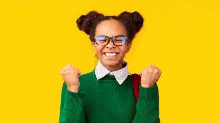 Photo pour Oui, je l'ai fait. Une adolescente afro hurle, faisant un geste de vainqueur sur fond de studio jaune, panorama - image libre de droit
