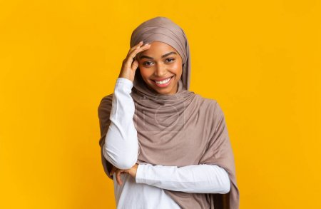 Photo for Shy modest black muslim girl in hijab touching her forehead and timidly looking at camera and smiling, yellow background with free space - Royalty Free Image