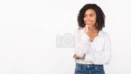 Photo pour Concept de plaisir. Portrait d'une femme noire rêvant avec un sourire de plaisir, regardant un espace de copie, un panorama - image libre de droit