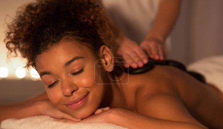 Photo pour Relaxed afro woman enjoying back stones massage in spa salon with candles on background - image libre de droit