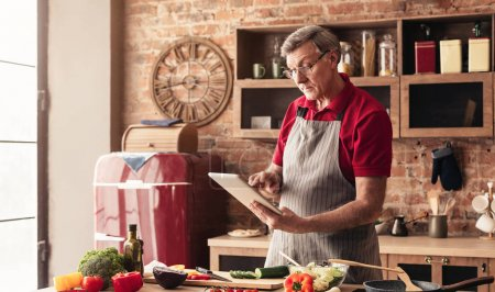 Photo pour Les technologies modernes et les aînés. Grand-père lisant la recette sur une tablette à la cuisine, préparant un repas santé, panorama, espace libre - image libre de droit