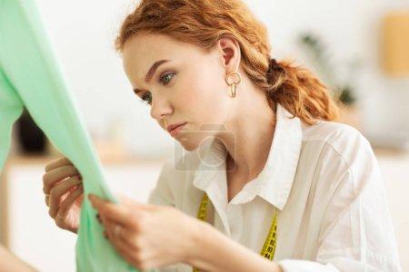 Photo pour Tailleur sérieux touchant et vérifiant un nouveau chandail, travaillant dans son propre atelier - image libre de droit