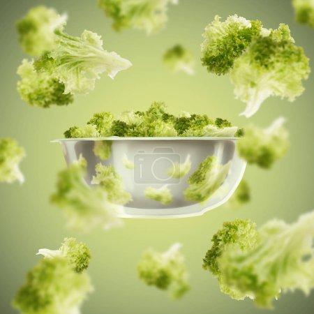 Photo pour Des verts en santé. Feuilles de salade volantes de l'assiette sur fond vert - image libre de droit