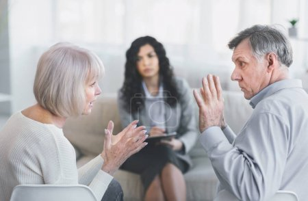 Photo for Conflict. Mature couple having fight in therapy or marriage counseling, waving hands, psychologist in the background - Royalty Free Image