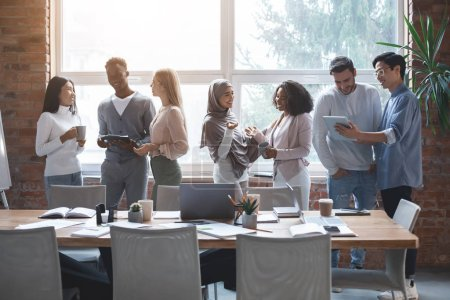 Photo pour Friendly international business team talking while having break at business meeting, office interior - image libre de droit