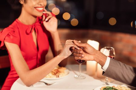 Photo for Loving Spouses Holding Hands Having Romantic Date Celebrating Anniversary Of Relationship Sitting In Restaurant. Cropped, Selective Focus - Royalty Free Image