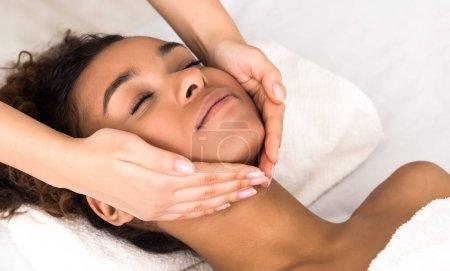 Photo pour Concept de cosmétologie. African-american woman enjoying face massage in spa salon, closeup - image libre de droit