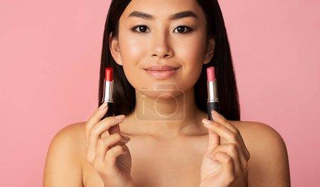 Photo pour Concept de maquillage. Fille asiatique tenant deux rouges à lèvres sur fond de studio rose, panorama - image libre de droit