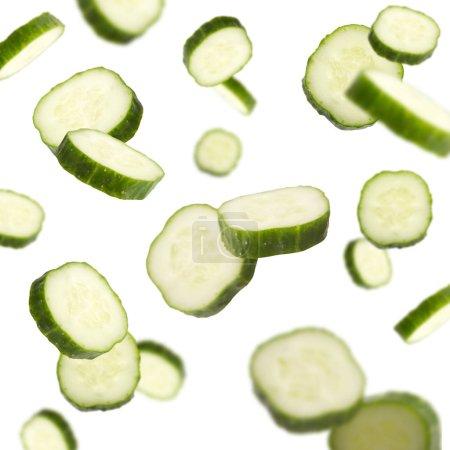 Photo pour Voler des concombres frais tombant sur un fond blanc. Salade de légumes et concept de saine alimentation - image libre de droit