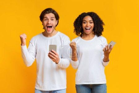 Photo pour Loto en ligne, Portrait d'un jeune homme et d'une jeune femme exaltés se réjouissant du succès de leur téléphone intelligent, s'exclamant triomphant sur fond jaune - image libre de droit
