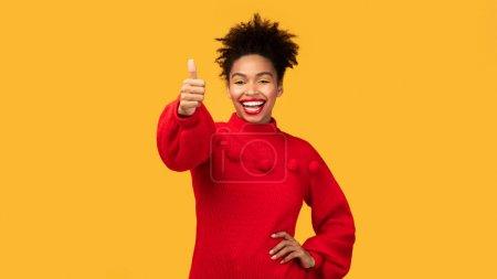 Photo pour Ça me plaît. Joyeux noir fille montrant pouces levés et largement souriant, isolé sur fond de studio orange, copyspace - image libre de droit
