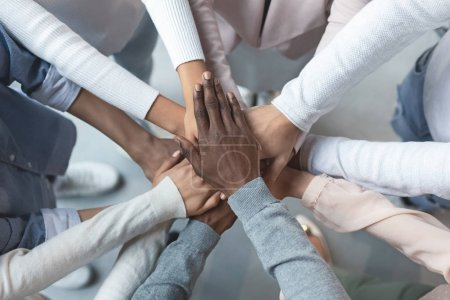 Photo for Top view of international business team showing cooperation with putting their hands together on top of each other - Royalty Free Image