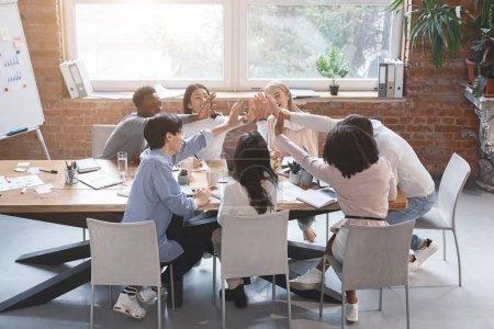 Photo pour Une jeune équipe d'affaires multiraciale donne cinq points après une réunion d'affaires réussie, espace de copie - image libre de droit