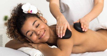Photo pour Femme détendue recevant un massage des bras aux pierres chaudes dans le spa. Concept de thérapie de beauté - image libre de droit