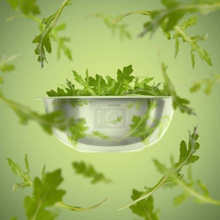 Photo pour Des verts en santé. Rucola volante de plaque sur fond vert - image libre de droit