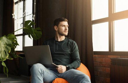 Photo for Freelance Lifestyle. Millennial Guy Working On Laptop Computer Sitting In Beanbag Chair In Modern Workspace Indoor - Royalty Free Image