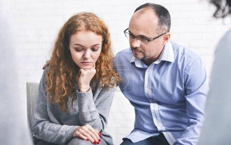 Photo pour Le mari aidant soutient sa femme déprimée lors d'une séance de thérapie matrimoniale au bureau des conseillers, l'encourageant à partager ses problèmes - image libre de droit