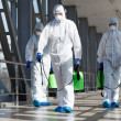 People in virus protective suits and mask disinfecting buildings of coronavirus with the sprayer,