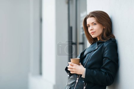 Photo for Happy casual brunette female staying near grey wall with coffee to go, after quarantine lifestyle, copy space - Royalty Free Image
