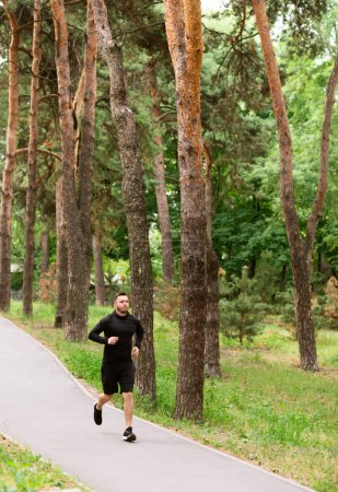 Photo for Training For Marathon. Male runner jogging on road, exercising outdoor in park near forest, vertical photo shot - Royalty Free Image