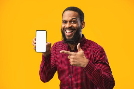 Photo for Smartphone Mock Up. Excited casual black man pointing at blank white cell phone screen, empty space, yellow studio - Royalty Free Image